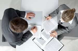 Image of two insurance brokers sitting at a table over paperwork.